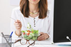 Young woman creative designer eating a salad  in office.